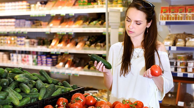Woman standing in the produce section of a grocery store with a tomato in one hand and a zucchini in the other looking concerned