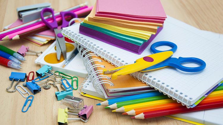 Open notebook surrounded by paper clips, lined up colored pencils, crazy scissors and color-coded sticky notes