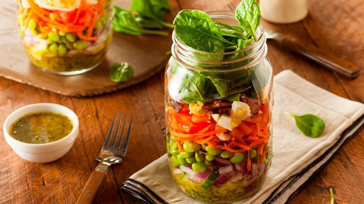 two large glass jars filled to the top with layers of different vegetables