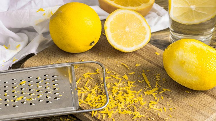 Three lemons and a grater sit on a wooden cutting board. One of the lemons is cut in half and a pile of zest sits in between all of them