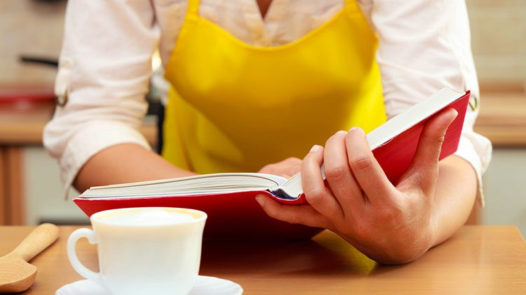 Person in a bright yellow apron leaning over a counter and reading a red book with a cup on a saucer in front of them