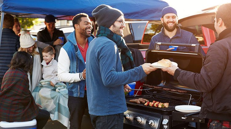 People dressed in sweaters, coats and laughing gathered around a grill filled with sausages