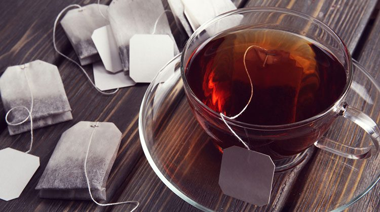 Glass cup filled with tea surrounded by tea bags on a wooden countertop