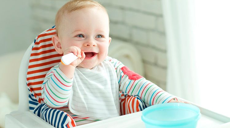 Smiling baby wearing a striped outfit and sitting in a high chair. One hand holding a spoon in their mouth and the other on the tray beside their blue bowl