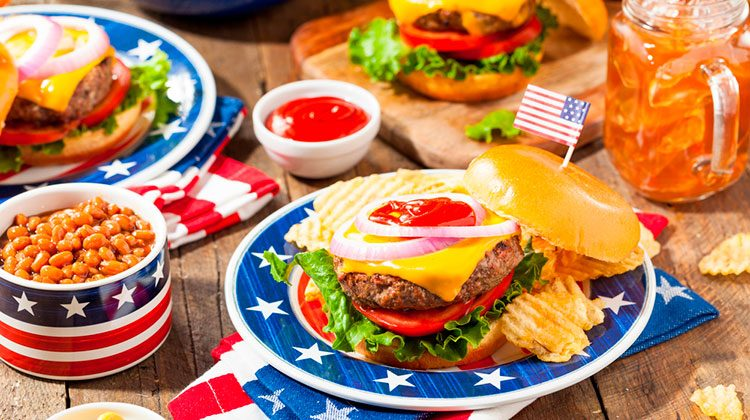 Large spread of juicy burgers loaded with toppings on red, white and blue plates, iced tea in mason jars, bowls of condiments and a bowl beans.