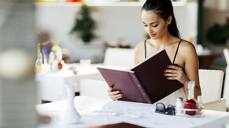 Woman in a black tank top looking over a menu as she sits at a table with a white tablecloth