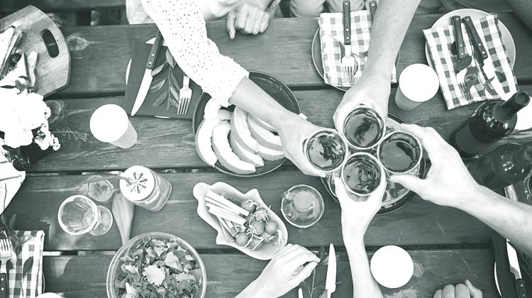 Black and white picture of a wooden picnic table covered with plates of food including slices of fruit, salads and bottles of wine. Four humans clink their glasses together