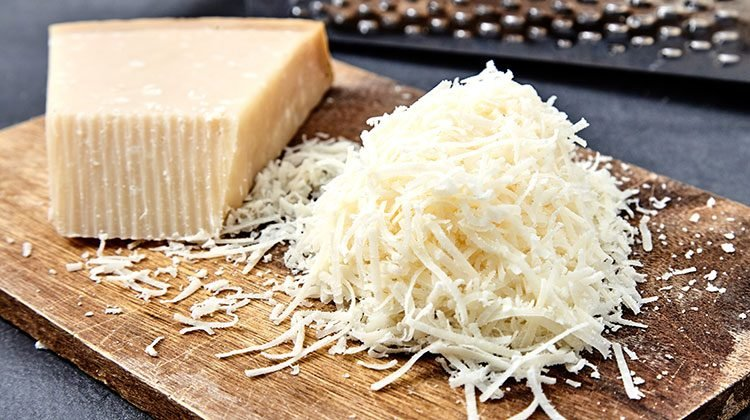 Chunk of cheese on a wooden cutting board beside a pile of shreds with a grater behind them