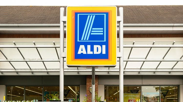 Large sign with the blue Aldi logo on it in front of a storefront littered with plants