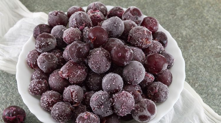 Frozen grapes piled up high in a white bowl