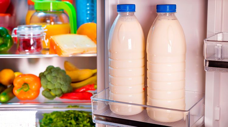 Two full jars of milk sit in the door shelf of the fridge door and the shelves are filled with produce
