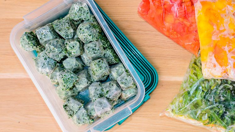 Tuber ware container filled with cubes of frozen kale sit beside three bags, each filled with a different color of sliced pepper