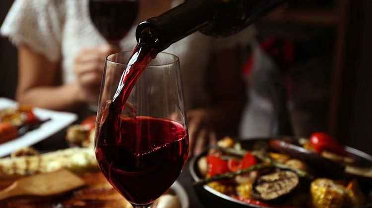 Red wine being poured into a glass on a table covered in plates full of food as people sitting around wait eagerly