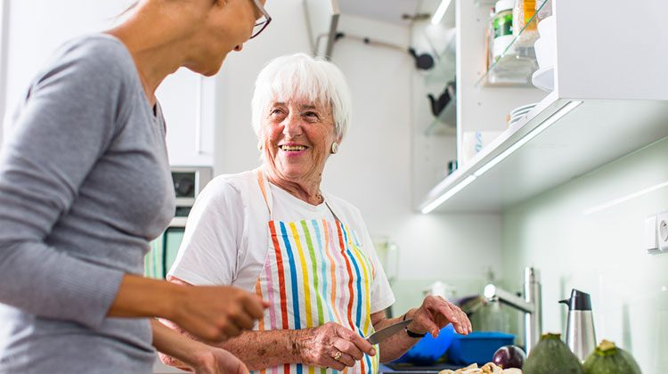 Grown daughter working along side her grandma in the kitchen with pan of brownies in hand. Grandma is holding a knife, in the process of dicing vegetables, but has stopped to turn and smile at the woman beside her