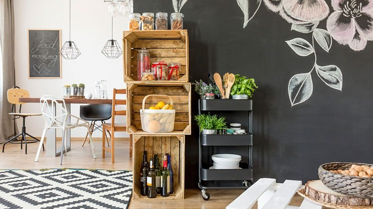 Large, well organized kitchen featuring crates used as shelves, floral patterns on black walls and a modern style kitchen table with four completely different chairs gathered around it