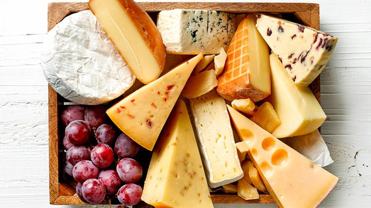 Multiple different cuts and types of cheeses piled together in a wooden box with a bunch of grapes taking up the lower left corner