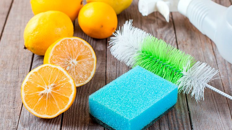 Five lemons laying beside a blue sponge, brush and spray bottle. One of the lemons is sliced in half, revealing its middle to the viewer