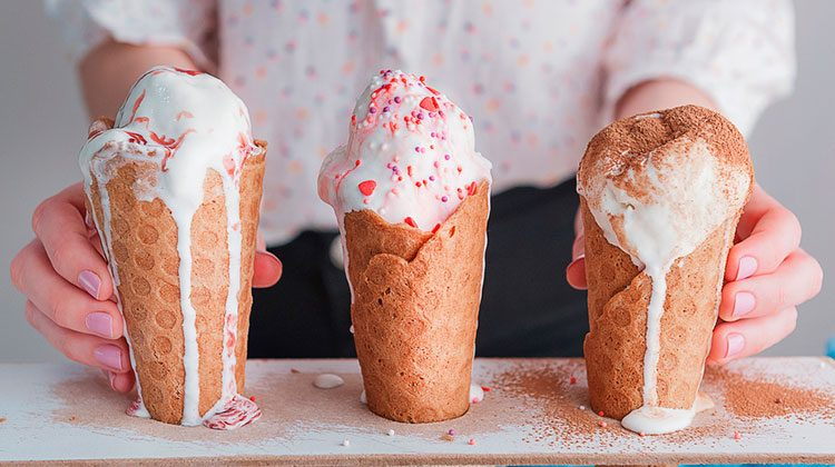 Person standing behind three melting ice cream cones. From left to right they are topped with berry topping, sprinkles, and chocolate powder