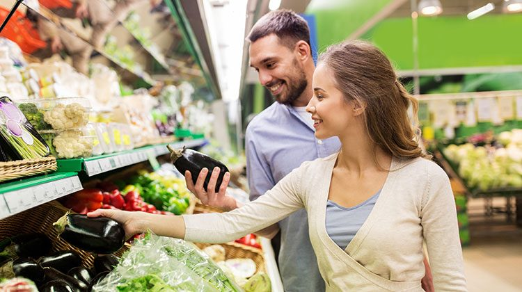 Man and woman in the produce section of a grocery store both reaching for eggplants and smiling