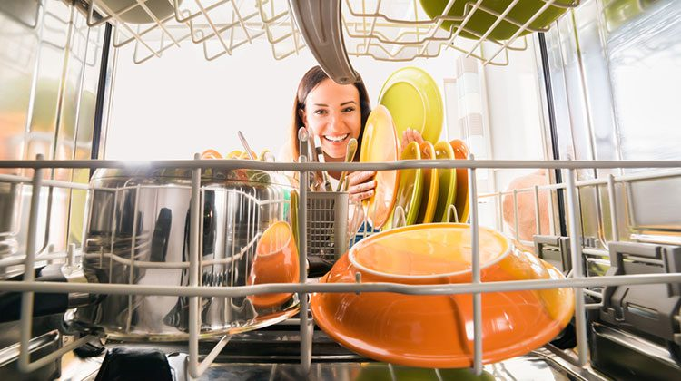 Woman reaching into her dishwasher to remove orange and yellow plates from the front row