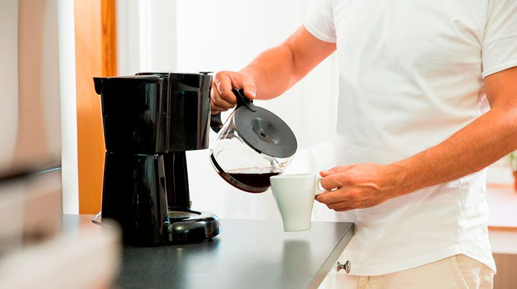 Person pouring coffee into their white mug from a coffee pot
