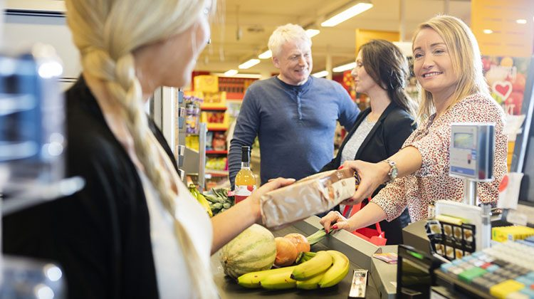 Woman handing a cashier a package of cookies over the counter with an unsure smile and another woman and man talk behind her in line