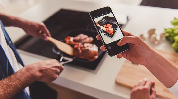 One person holding up a smartphone and filming another person as they grill meat in a skillet on the stovetop