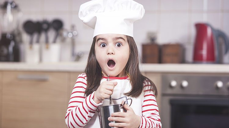 Young girl in a red and white striped shirt holding a small metal pot in one hand and a whisk in the other. Her mouth is open wide in surprise
