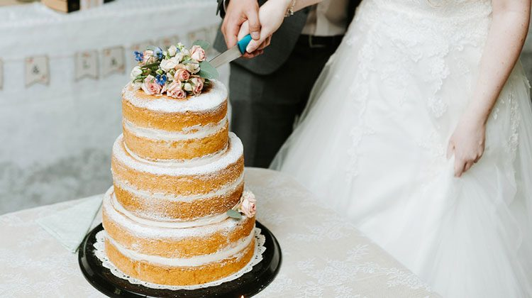 Bride and groom with conjoined hands on a knife, slicing into a three-tiered vanilla cake with no frosting that is topped with pink flowers