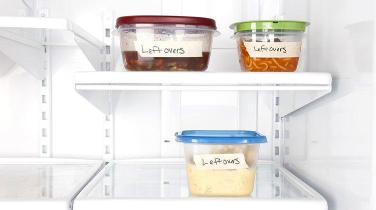 Fridge with three tuber ware containers inside, each with a different colored lid and labelled with the word 'leftovers'