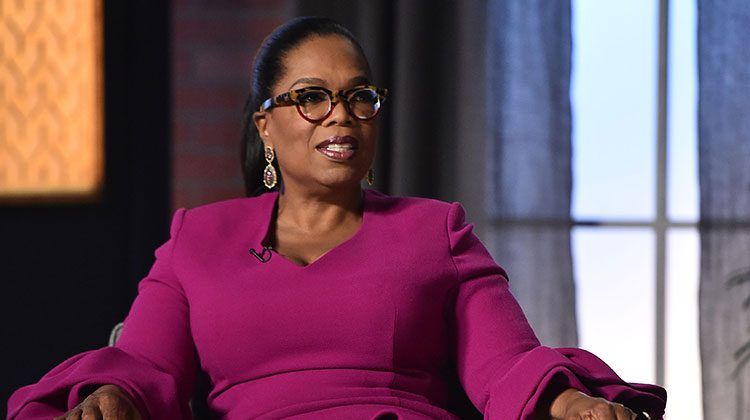 Oprah wearing a magenta dress relaxing back into a chair with her eyes looking to the right off-screen