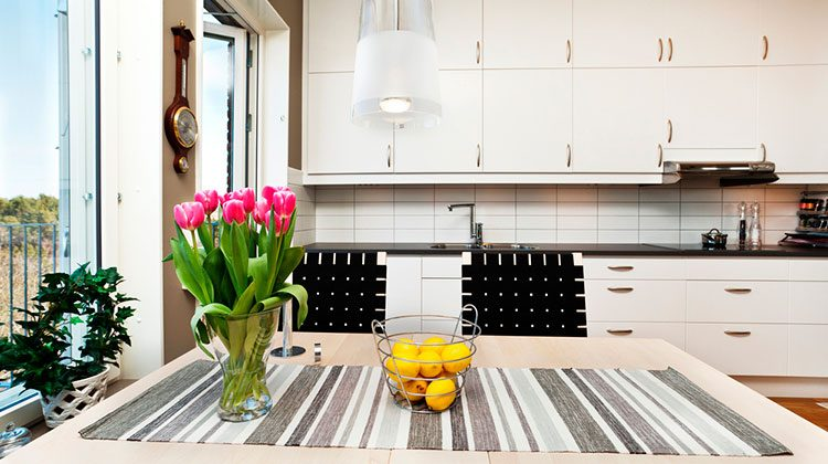 Modern style kitchen with double rows of cabinets, large floor length windows and a table minimally decorated with pink tulips, a wire basket of lemons and a gray striped cloth