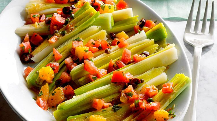 Sicilian Steamed Leeks sitting on a dinner table beside a fork