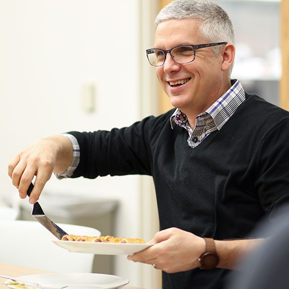 Man smiling and using a spatula to pick up food from a plate in his hand