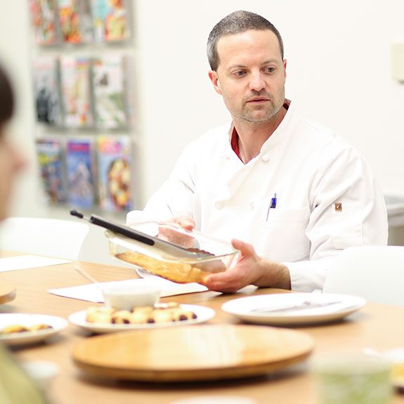 Matthew Hass, test cook collecting an empty glass pan and listening to feedback at a taste testing