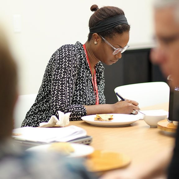 woman writing in her notebook after tasting a dish