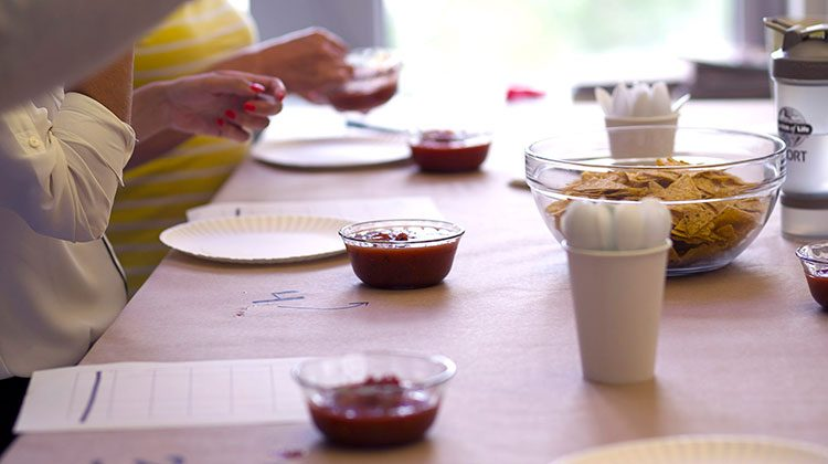 People standing around a table with a row of plastic bowls filled with salsa and one large glass bowl of tortilla chips