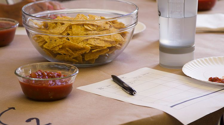 Large glass bowl of tortilla chips and a smaller bowl of salsa on a table beside a piece of paper featuring a chart and a pen