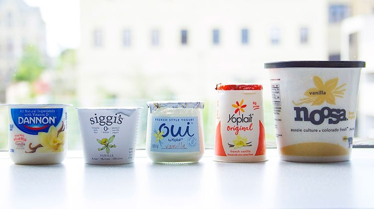 5 different brands of yogurt containers lined up in front of a window