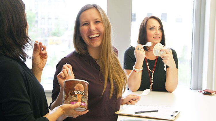 Nicole Doster reaching a spoon into a carton of Edy's chocolate ice cream being held out to her