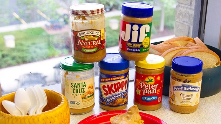 Different brands of peanut butters stacked on top of one another like a pyramid. A red plate is front of them with a dollop of peanut butter on it and to the side is a yellow basket filled with utensils