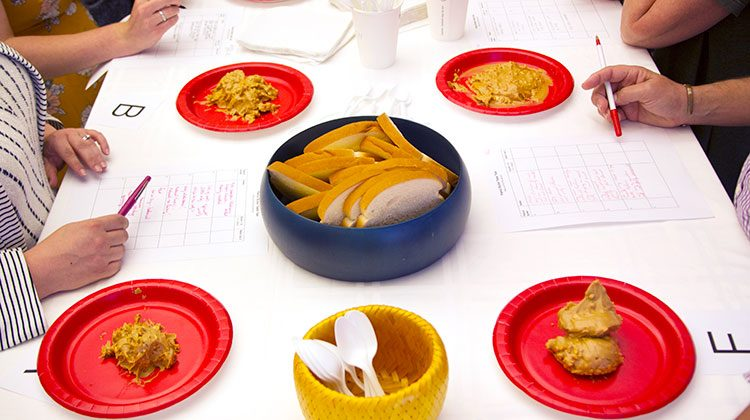 Red plates with dollops of peanut butter on them spread out evenly between sheets of notes and bowls of utensils and bread