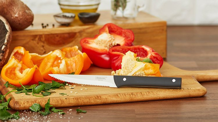 Steak knife on a wooden cutting board in front of sliced orange and red peppers