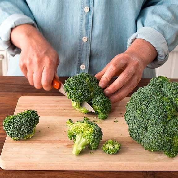 Chopping broccoli on a cutting board.