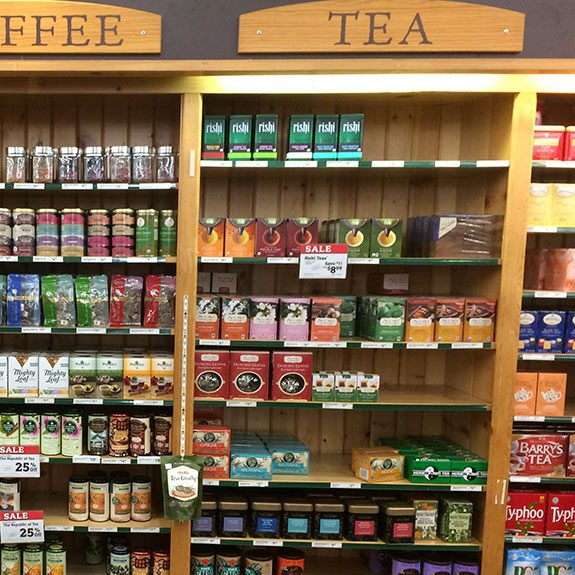 Wooden shelves filled with boxes of tea set into a wall with a sign labelling them as Tea nailed above