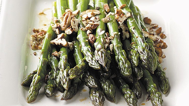 cooked asparagus piled together on a plate and topped with nuts