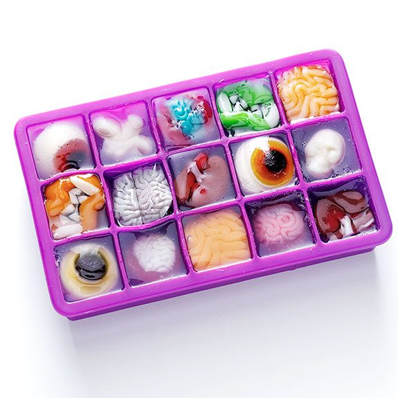Purple ice cube tray full of jello with monster-themed gummies inside including eyeballs, vampire teeth, organs and more