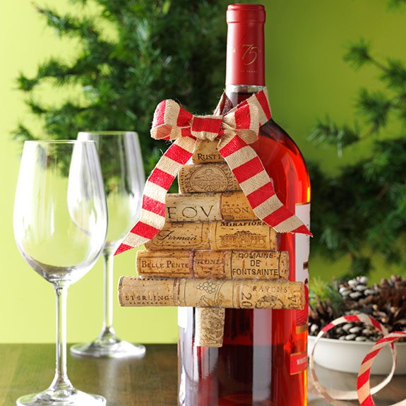 Wine corks are arranged into a tree and glued into a new wine bottle with a red striped ribbon as decoration