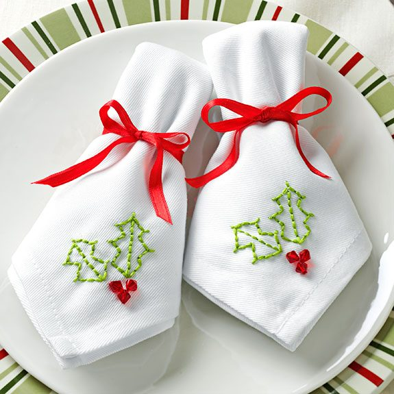 Two folded cloth napkins sit side-by-side on a plate. Each has the outline of a holly leaf stitched into it