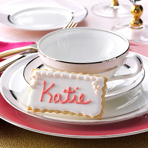Rectangle sugar cookie decorated with white icing and pink letters that spell out Katie. It rests against a white and pink tea cup on several similarly colored plates